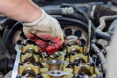 Demonteerde de interne verbrandingsmotor, maakt de hand van de hersteller de cilinderkop schoon stock foto
