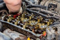 Demonteerde de interne verbrandingsmotor, maakt de hand van de hersteller de cilinderkop schoon stock foto's
