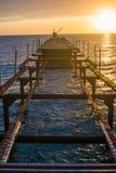 Demontera gammal pir f?r skepp ?ver havet p? solnedg?ngen arkivbilder