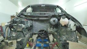 Demonterad framdel av en bil i garaget lager videofilmer
