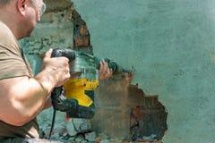 Demontering av väggar och av öppningar med en elektrisk tryckluftsborr Arbetaren i skyddsglasögon utför reparationsarbete royaltyfria bilder