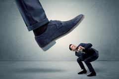 Employee getting trampled by big shoe Royalty Free Stock Photography
