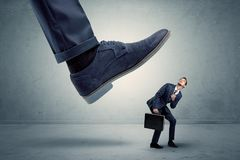 Employee getting trampled by big shoe. Demoralised employee symbolized by small man getting trampled stock photos