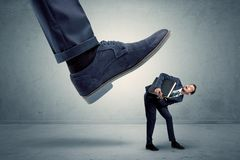 Employee getting trampled by big shoe. Demoralised employee symbolized by small man getting trampled royalty free stock photos