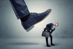 Employee getting trampled by big shoe. Demoralised employee symbolized by small man getting trampled stock image