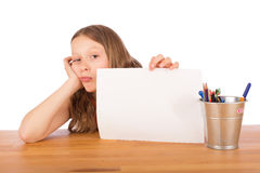 Demoralized child shows a white sheet. Demoralized child sitting at a wooden table shows a white sheet of paper. Isolated on a white background Royalty Free Stock Photos