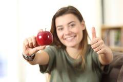 Demostración adolescente sana una manzana en casa Fotos de archivo libres de regalías