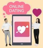 Demostración alegre de los pares en línea que fecha en una tableta fotografía de archivo