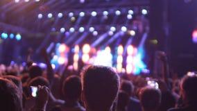 Demostración asombrosa de observación de mucha gente en la etapa iluminada, ejecución de la banda de la música almacen de video