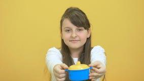 Demostración bonita de la niña un pote plástico en el fondo amarillo almacen de metraje de vídeo