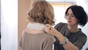 Demostración de la mujer cómo atar una bufanda alrededor del cuello del modelo almacen de metraje de vídeo