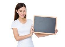 Demostración de la mujer joven con la pantalla en blanco de la pizarra Foto de archivo libre de regalías