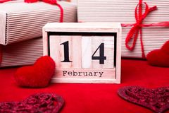 Demostración de madera del calendario del 14 de febrero con las cajas rojas del corazón y de regalo Foto de archivo libre de regalías