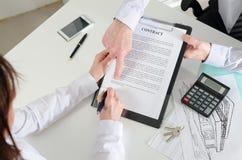 Demostración del agente inmobiliario donde firmar el contrato de las propiedades inmobiliarias Imagenes de archivo