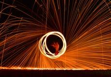 Demostración del bombero en el hombre de la danza de la playa que hace juegos malabares con el balneario del fuego del oscilación Foto de archivo