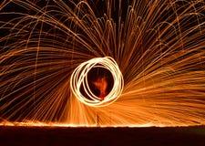 Demostración del bombero en el hombre de la danza de la playa que hace juegos malabares con el balneario del fuego del oscilación Imagen de archivo