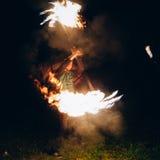 Demostración del fuego en la noche El hombre se coloca delante de Imágenes de archivo libres de regalías