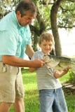 Demostración del Grandpa cómo sostener un pescado Imagen de archivo