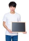Demostración del hombre joven con la pizarra Fotos de archivo libres de regalías