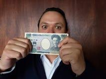 demostración del hombre joven y sostener un billete de banco japonés de 1000 yenes fotos de archivo libres de regalías