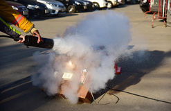 Demostración del instructor cómo utilizar un extintor en un entrenamiento Imagen de archivo