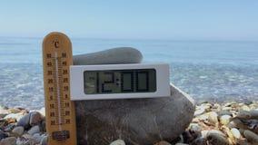Demostración del termómetro la temperatura del aire en el mediodía en la playa almacen de metraje de vídeo