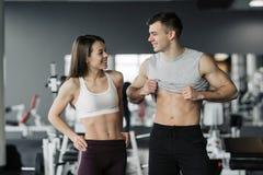 Demostración deportiva de los pares de la aptitud en gimnasio Hombre y mujer atl?ticos hermosos, ABS muscular del torso foto de archivo
