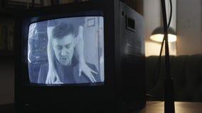 Demostración dinámica de centellar la pantalla anticuada de la TV con el canto del hombre joven metrajes