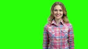 Demostración feliz de la mujer algo en la pantalla verde almacen de video