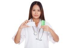 Demostración femenina joven asiática del doctor una tarjeta en blanco con la medicina Imagenes de archivo