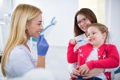 Demostración femenina joven del dentista cómo lavar los dientes fotos de archivo