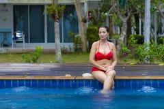 Demostración grande del cuerpo de la mujer atractiva con el bikini rojo en la piscina Fotos de archivo