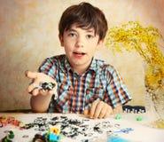 Demostración hansome del muchacho del preadolescente el resultado de su afición p del telar del arco iris Foto de archivo libre de regalías