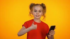 Demostración linda de la muchacha que mecanografía y que señala en el teléfono, guiñando y mostrando los pulgares-para arriba metrajes