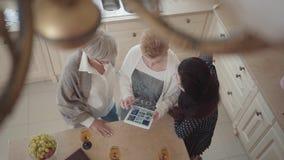 Demostración mayor de la mujer a sus fotos de los amigos en la tableta El grupo del centro tres envejeció a las mujeres maduras q almacen de video