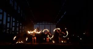 Demostración profesional del fuego en el hangar viejo de los aviones mostrar a artistas profesionales del circo tres mujeres en l almacen de metraje de vídeo