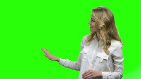 Demostraci?n sonriente de la mujer algo en la pantalla verde almacen de metraje de vídeo