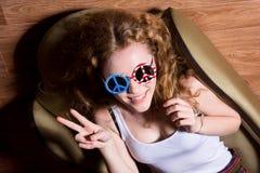 Demostración Victory Sign de la chica joven que sonríe con el sol que lleva del pelo rizado Imagen de archivo libre de regalías