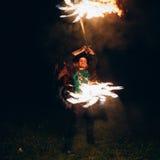 Demostración del fuego en la noche El hombre joven se coloca delante de Foto de archivo libre de regalías