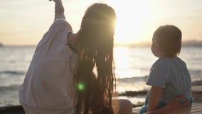 Demostraciones de la mamá al bebé algo en el cielo, estando cerca del mar en la cámara lenta almacen de metraje de vídeo