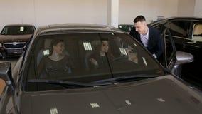 Demostraciones del consultor de las ventas a chicas j?venes un nuevo coche a comprar almacen de video