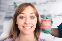 Demostraciones del dentista cómo aplicar un apoyo fotografía de archivo libre de regalías