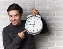 Demostraciones del hombre joven en el reloj Fotos de archivo