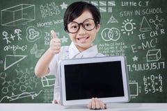 Demostraciones lindas tableta y pulgar de la muchacha para arriba en clase Fotos de archivo libres de regalías