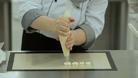 Demostration of a cooking syringe used for buttercream covering. Buttercream is squeezed out of a cooking syringe on a smooth surface by female hands. It looks stock video footage