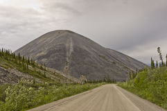 Demster Highway leading to a distinctive eroded mountain Royalty Free Stock Images