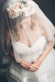 Demure bride with her veil over her face. High angle view of a demure bride with flowers in her hair and her veil over her face sitting looking down at her Stock Image