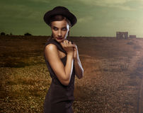 Demure elegant young woman. In a stylish hat and dress posing with downcast eyes and her hands raised to her chim in a gloomy atmospheric landscape Stock Image