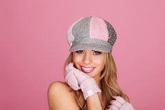 Demure Woman In Peaked Cap. Pretty demure young woman wearing pink winter mitts and coordinated fabric peaked cap Stock Photos