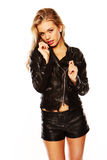 Demure young blonde in leather. Jacket and shorts isolated on white Stock Photos